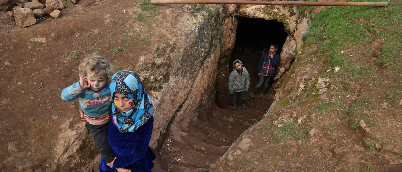 Children walk through the entrance of an underground shelter where several families of internally displaced Syrians from Aleppo and Idlib provinces are taking refuge, in the village of Taltunah about 15 kilometers northwest of Idlib in the northwestern Idlib province, Feb. 23, 2020. (AFP Photo)