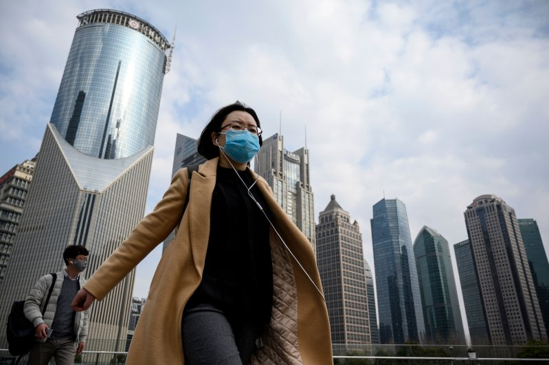 People wearing protective face masks walk on an overpass in Shanghai on February 25, 2020. (AFP Photo)