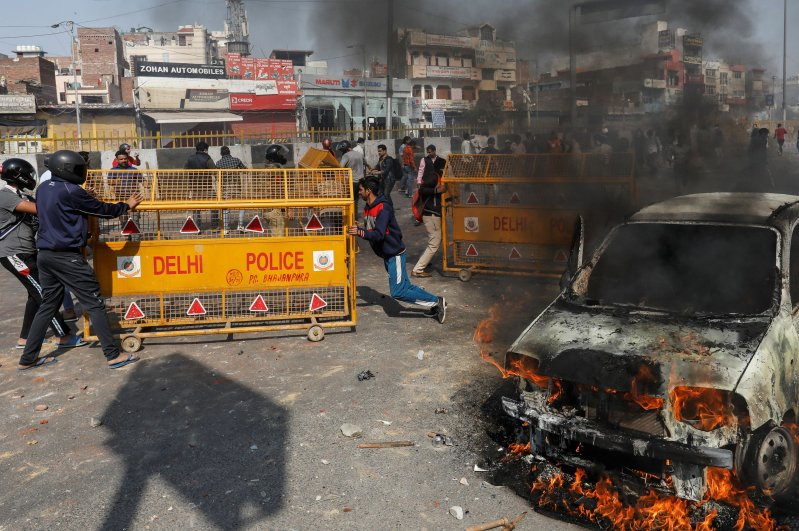 People supporting a new citizenship law push police barricades during a clash with those opposing the law, New Delhi, Feb. 24, 2020. (Reuters Photo)