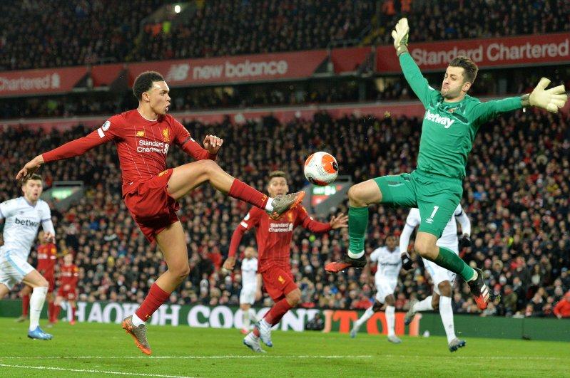 Trent Alexander-Arnold (L) of Liverpool beats West Ham goalkeeper Lukasz Fabianski to give the assist, Liverpool, Feb. 24, 2020. (EPA Photo)