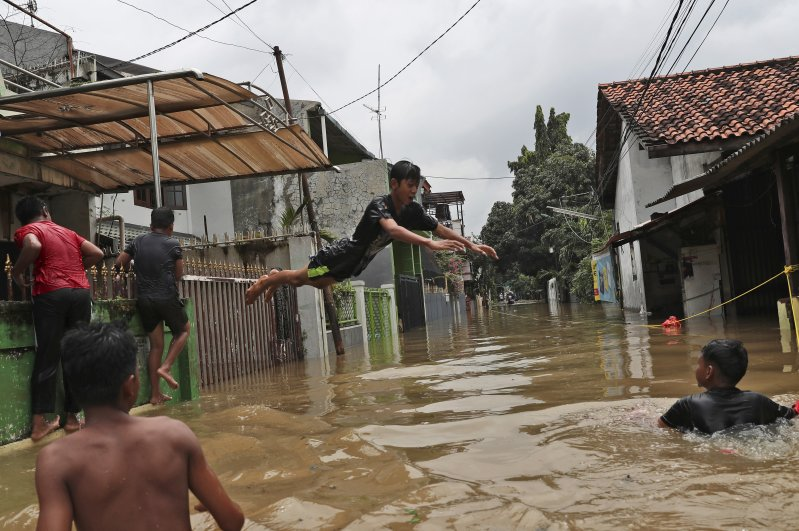 Indonesian youths play in flood water in a neighborhood in Jakarta, Indonesia, Tuesday, Feb. 25, 2020. (AP Photo)