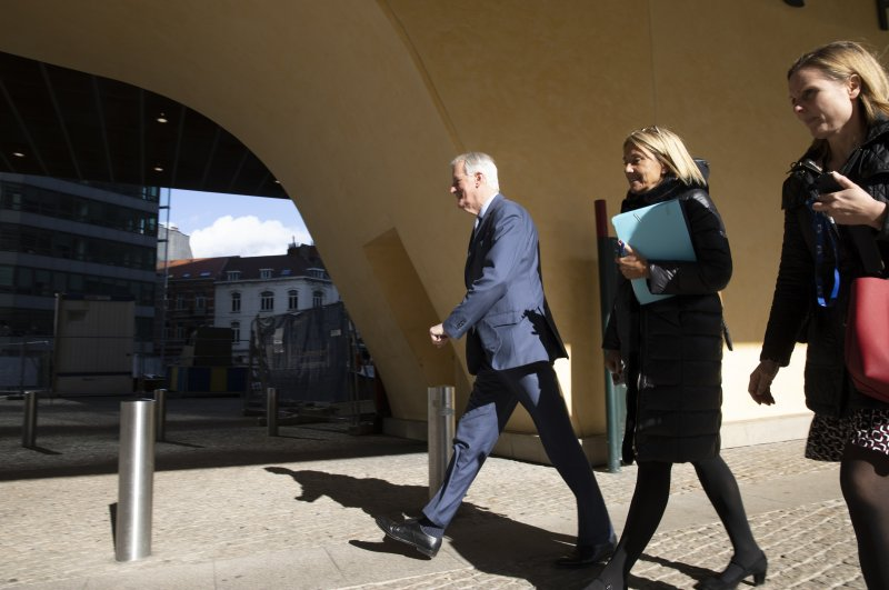 EU chief Brexit negotiator Michel Barnier (L) walks to a General Affairs Council meeting from EU headquarters in Brussels, Tuesday, Feb. 25, 2020. (AP Photo)