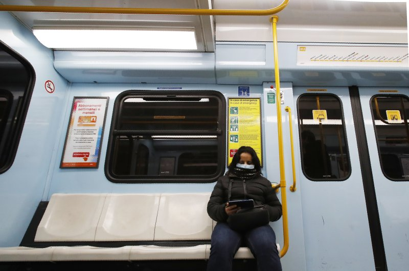 A woman wearing a face mask checks her phone in a subway in Milan, Italy, Tuesday, Feb. 25, 2020. (AP Photo)
