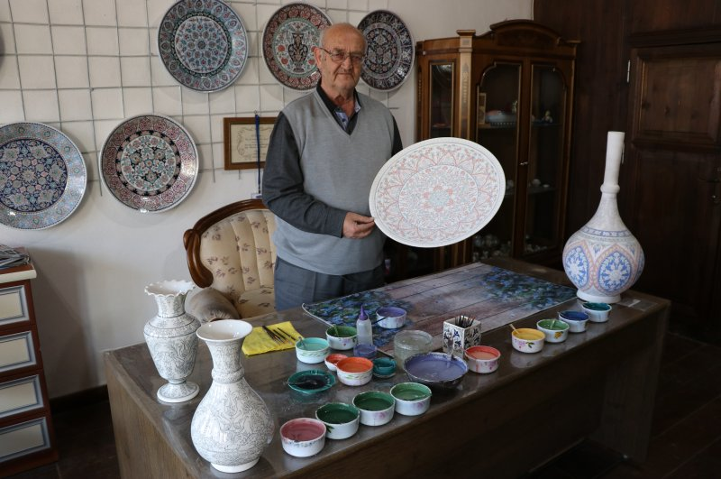 Hamza Üstünkaya poses with some of his works. (AA Photo)