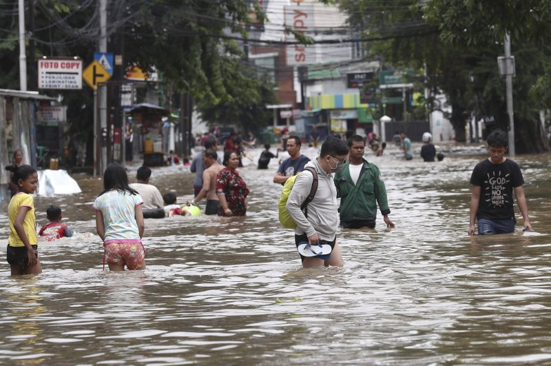 Indonesians wade through floodwater on a street in Jakarta, Feb. 25, 2020. (AP Photo)