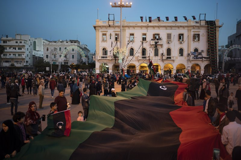 People carry a giant Libyan flag in Martyrs' Square during a march commemorating the anniversary of anti-Gadhafi protests in Tripoli, Libya, Feb. 25, 2020. (AP Photo)