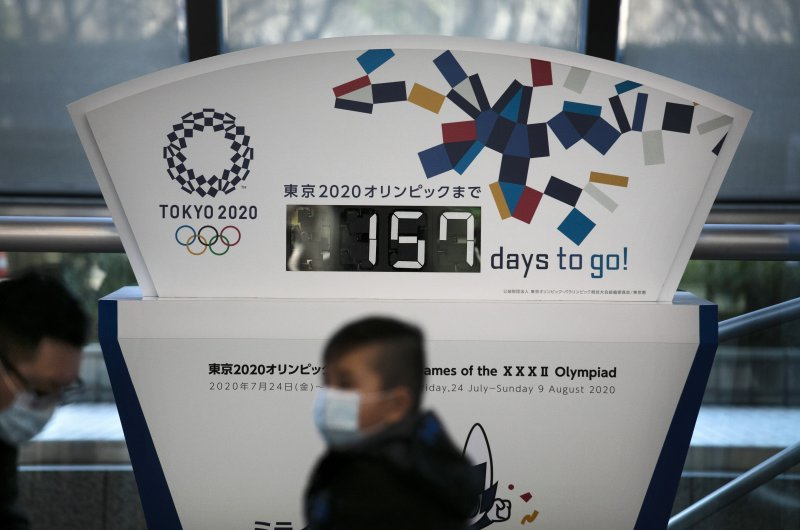 People wearing masks sit in front of a countdown clock for the 2020 Olympics in Tokyo, Feb. 18, 2020. (AP Photo)