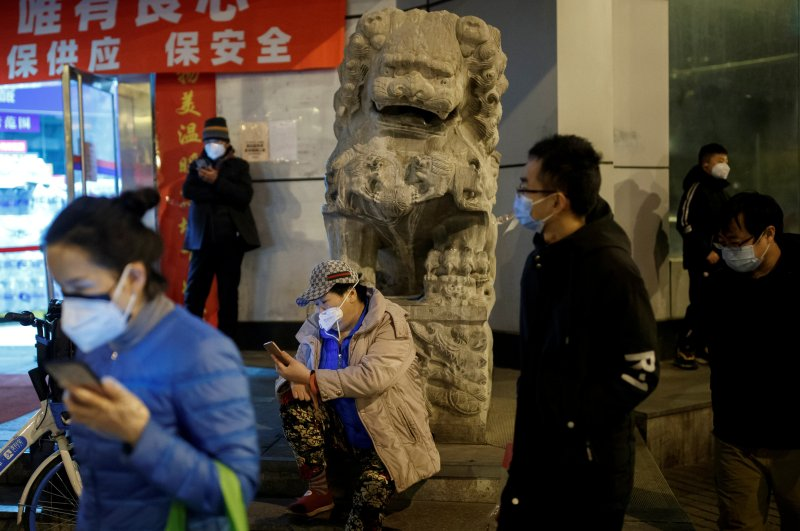People wear face masks in a street in Beijing, China, Feb. 26, 2020. (Reuters Photo)