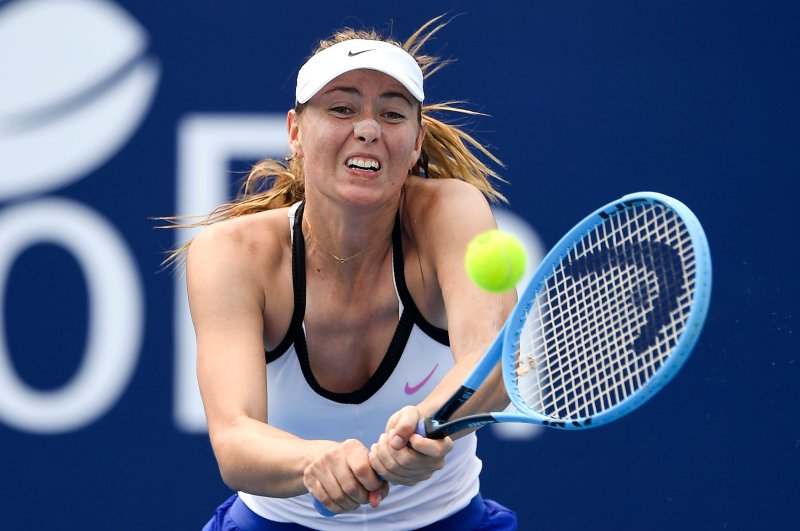 This Jan. 13, 2020, file photo shows Maria Sharapova of Russia hitting a return during her match with Laura Siegemond of Germany which was abandoned due to the smoke from bushfires at the Kooyong Classic tennis tournament, in Melbourne, Australia. (AFP Photo)
