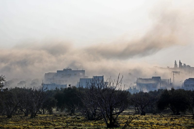 Smoke billows above buildings during an air strike by pro-regime forces on the village of Nayrab, about 14 kilometres southeast of the city of Idlib in northwestern Syria, Feb. 25, 2020. (AFP)