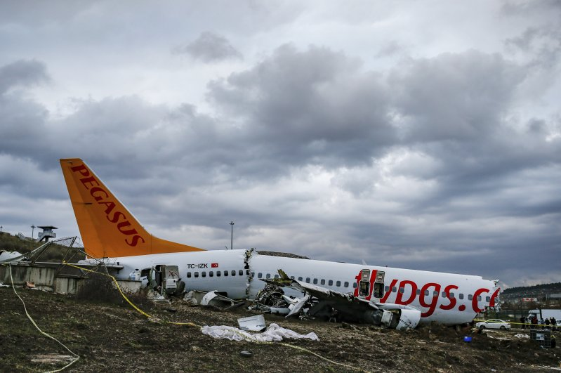 Workers prepare to remove the wreckage of the Pegasus plane after the crash at Sabiha Gökçen Airport, Istanbul, Feb. 7, 2020. (AP Photo)