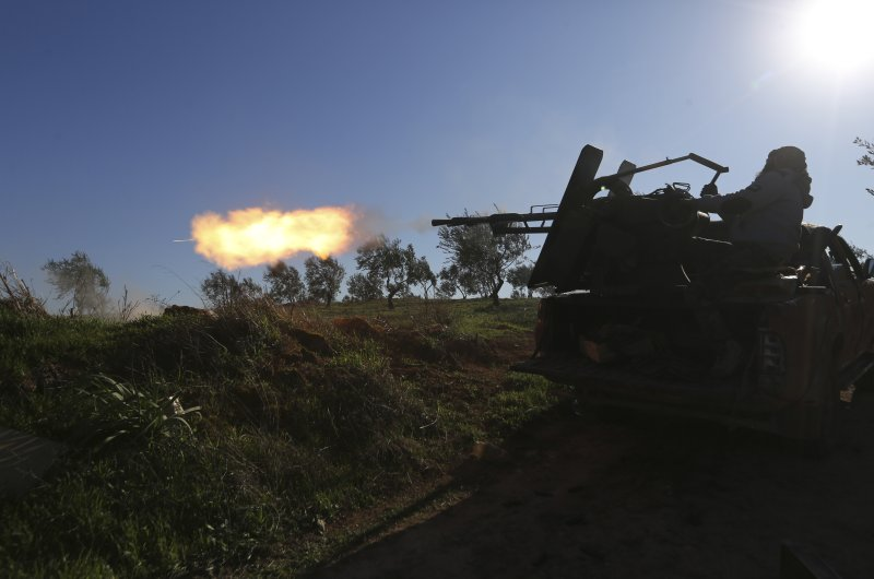 Turkish backed Syrian fighter fires at a frontline near the town of Saraqib in Idlib province, Syria, Wednesday, Feb. 26, 2020. (AP Photo)