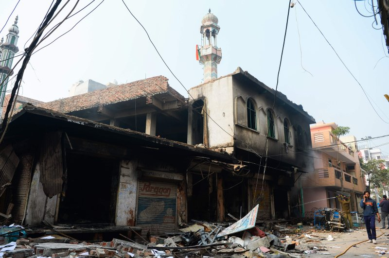 The photo shows a burnt-out mosque and shops following clashes, New Delhi, Feb. 26, 2020. (AFP Photo)