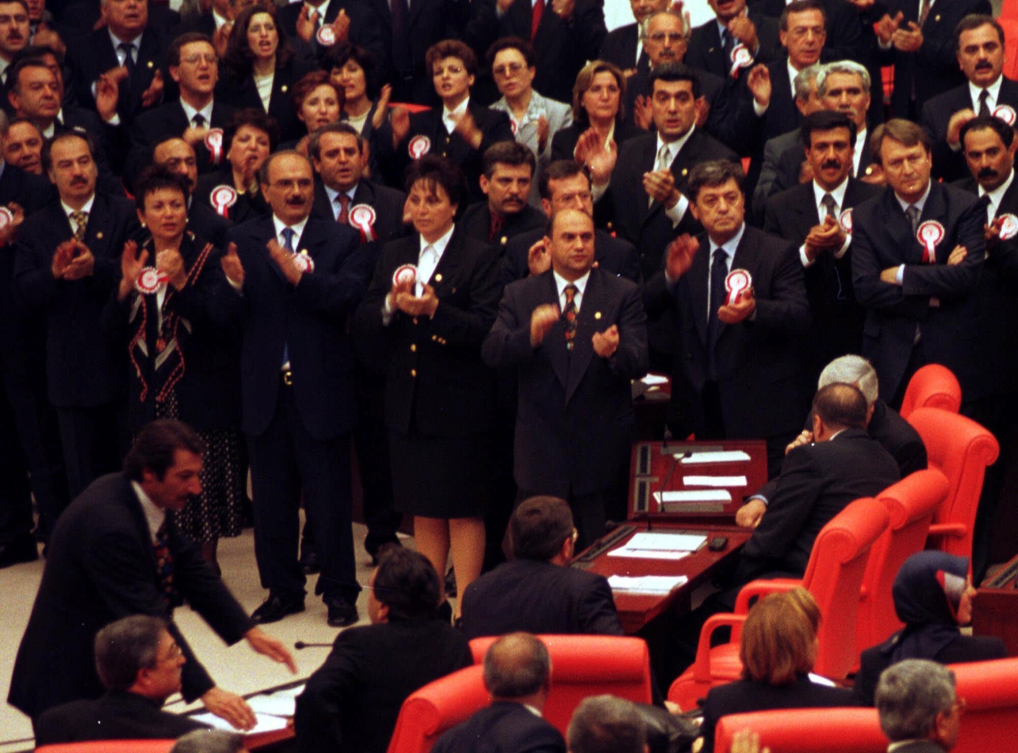 Wearing a headscarf Merve Kavakçı, a female new deputy of pro-Islamic Virtue Party at that time, bottom right, looks around as social democrat deputies protest her in the Parliament hall in Ankara, May 2, 1999. (AP Photo)