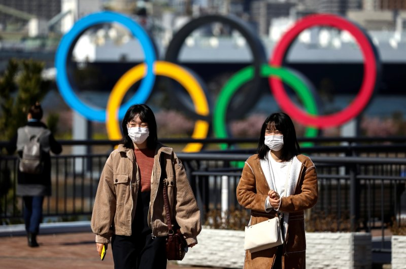 People wearing protective face masks are seen in front of the Giant Olympic rings at the waterfront area at Odaiba Marine Park, Tokyo, Feb. 27, 2020. (REUTERS Photo)