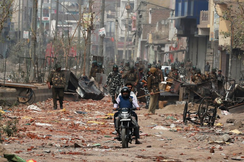 Men ride a motorcycle past security forces patrolling a street in a riot-affected area after clashes erupted over the new anti-Muslim citizenship law in New Delhi, India, Feb. 26, 2020. (REUTERS Photo)