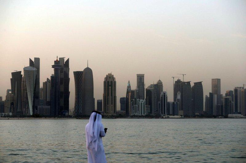 A man looks at his phone on the corniche of the Qatari capital Doha, July 2, 2019. (AFP Photo)