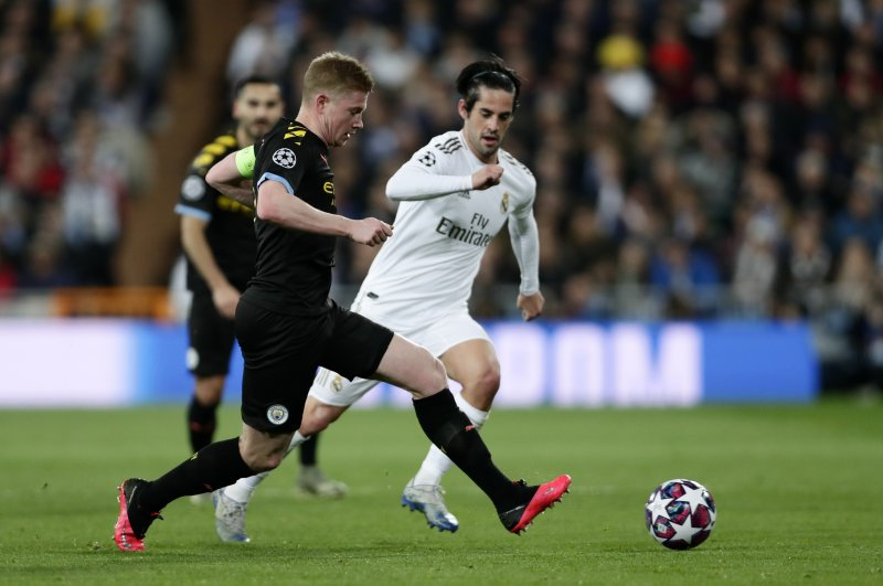 Manchester City's Kevin De Bruyne, left, duels for the ball with Real Madrid's Isco during the Champions League, round of 16, first leg soccer match between Real Madrid and Manchester City at the Santiago Bernabeu stadium in Madrid, Spain, Feb. 26, 2020. (AP Photo)