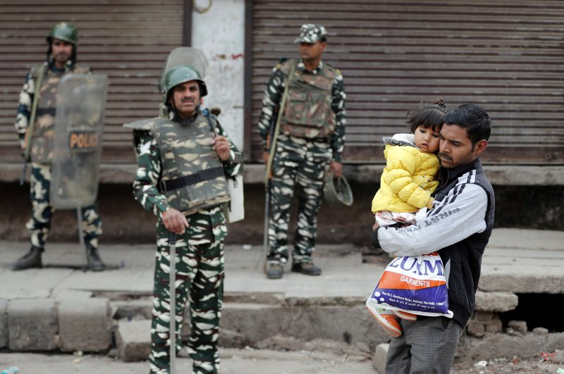 A man carrying a child walks past security forces in a riot affected area following clashes between people demonstrating for and against a new citizenship law, New Delhi, Feb. 27, 2020. (REUTERS Photo)