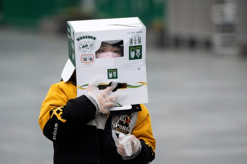 A boy wears a cardboard box on his head at the Shanghai Railway station in Shanghai on Feb. 13, 2020. (AFP Photo)