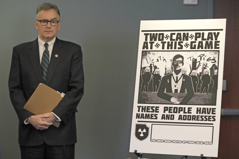 U.S. Attorney Brian Moran stands next to a poster that was mailed earlier in the year to the home of an investigative reporter, Seattle, Feb. 26, 2020. (AP Photo)