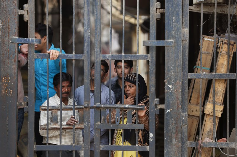 Residents look from behind a closed iron gate of their alley in Karaval Nagar following violence in New Delhi, India, Feb. 27, 2020. (AP Photo)