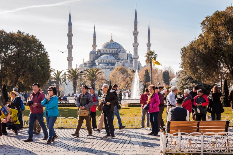 Tourists walk and snap photos in front of the Blue Mosque in Sultanahmet district, Istanbul, Nov. 25, 2017.