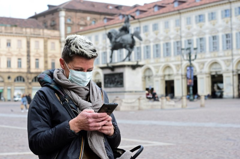 A woman wearing a protective mask uses her mobile phone, Turin, Feb. 27, 2020. (REUTERS Photo)