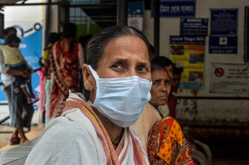 An elderly woman wearing a protective facemask sits with other patients at the Siliguri District Government hospital, Siliguri, Feb. 21, 2020. (AFP Photo)
