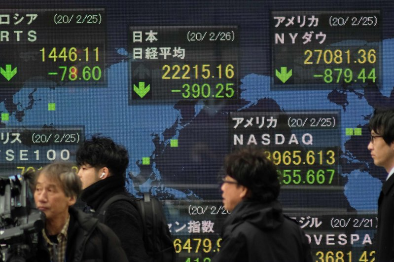 Pedestrians walk past an electronic quotation board displaying share prices of the Nikkei 225 Index (C, top) and other global stock markets in Tokyo, Feb. 26, 2020. (AFP Photo)