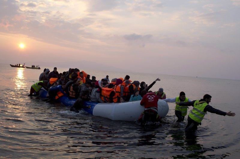 In this March 20, 2016 file photo, volunteers help migrants and refugees on a dingy as they arrive at the shore of the northeastern Greek island of Lesbos, after crossing the Aegean sea from Turkey. (AP Photo)