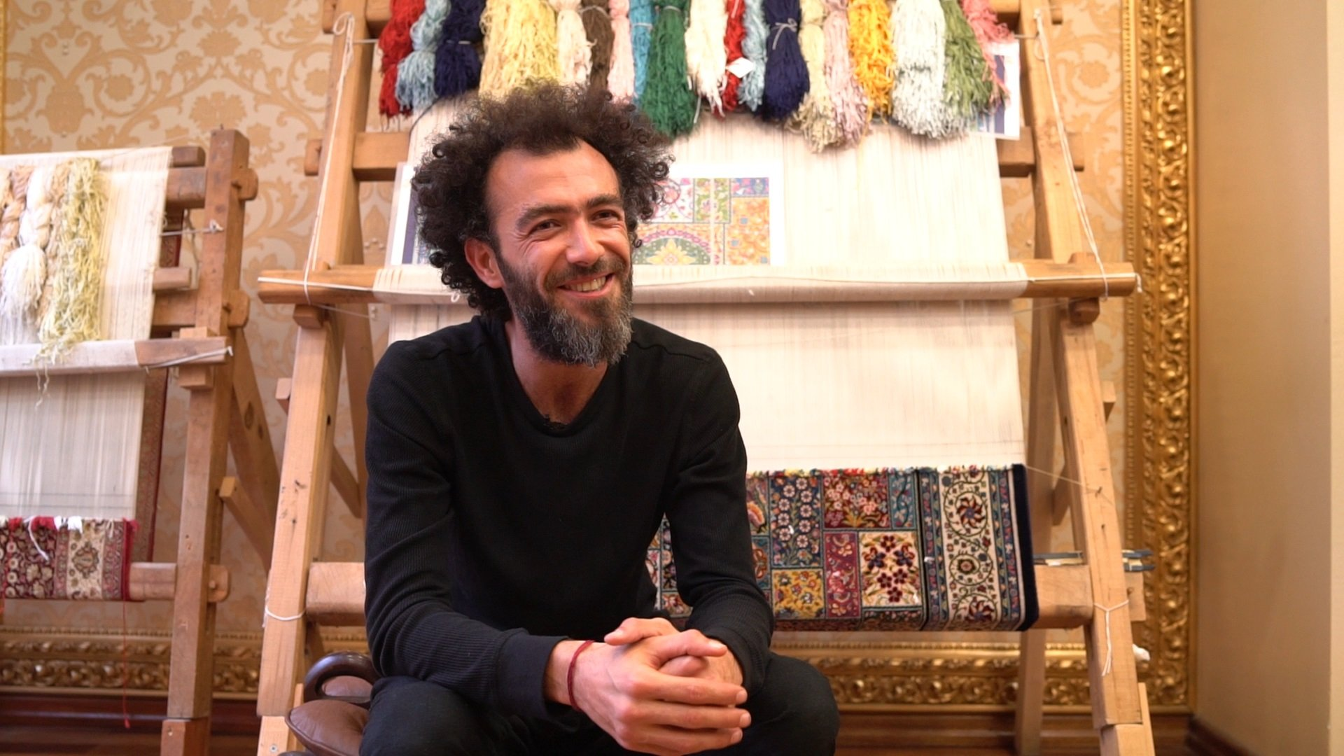 Faig Ahmed poses with his silk carpet woven with diverse threads. (Courtesy of Istanbul Modern)