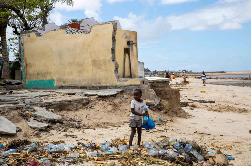 A child collects plastic bottles next to a house destroyed by cyclone Idai in 2019, in the Praia Nova neighbourhood in Beira, Mozambique, Feb. 26, 2020. (AFP Photo)
