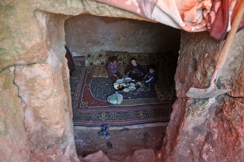 A family of internally displaced Syrians eats together in an underground shelter where several families from Aleppo and Idlib provinces are taking refuge in the village of Taltunah, about 15 kilometers northwest of Idlib city in northwestern Idlib province, Feb. 23, 2020. (AFP Photo)