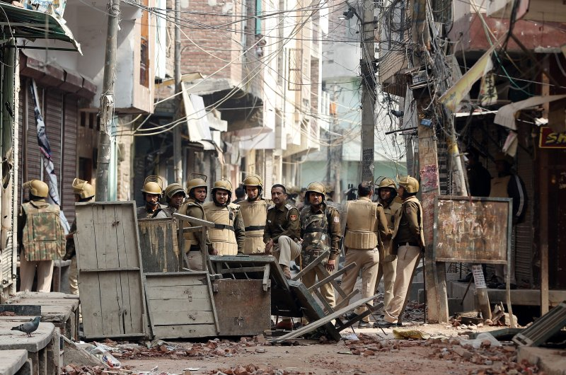 Police officers stand guard in an alley in a riot-affected area following clashes, New Delhi, Feb. 28, 2020. (Reuters Photo)