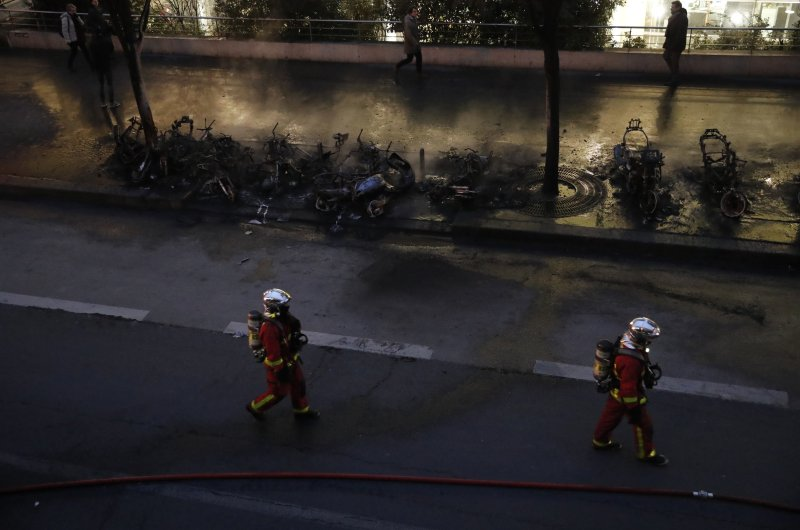 Firefighters walk past charred vehicles after a fire near the Gare de Lyon train station Friday, Feb. 28, 2020 in Paris. (AP Photo)