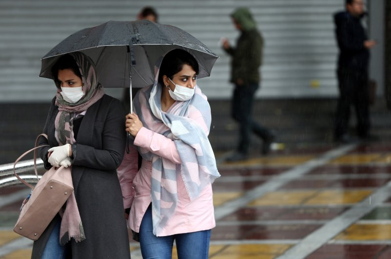 Iranian women wear protective masks to prevent contracting coronavirus, as they walk in the street in Tehran, Iran, Feb. 25, 2020. (WANA via Reuters Photo)
