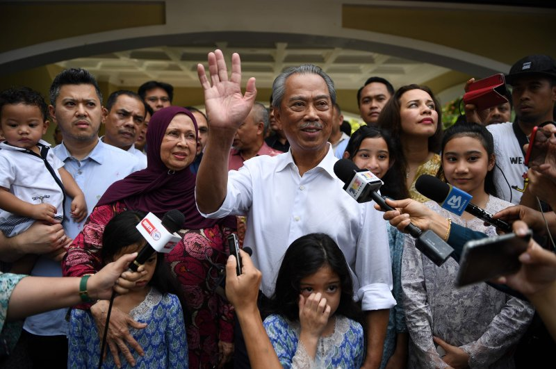 Malaysia's former interior minister Muhyiddin Yassin (C) and his family wave to the press shows outside his home in Kuala Lumpur on Feb. 29, 2020. (AFP Photo)