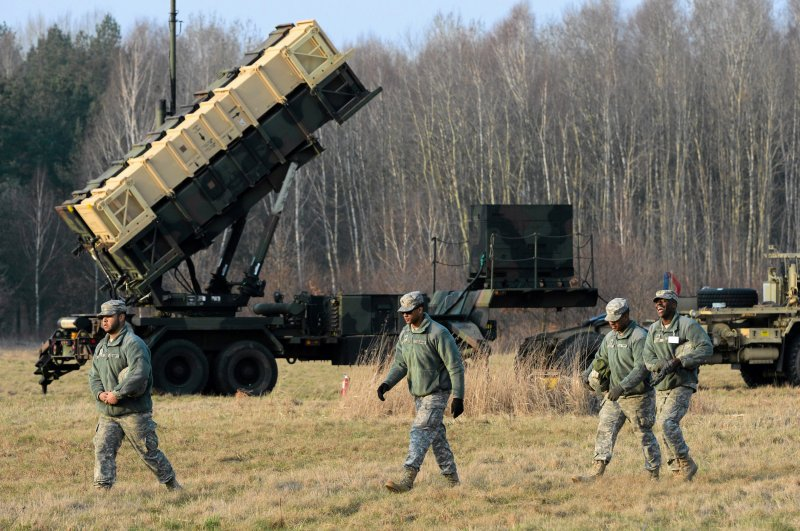 U.S soldiers walk next to a Patriot missile defense battery during join exercises at the military grouds in Sochaczew, Poland, March 21, 2015. (Reuters Photo)