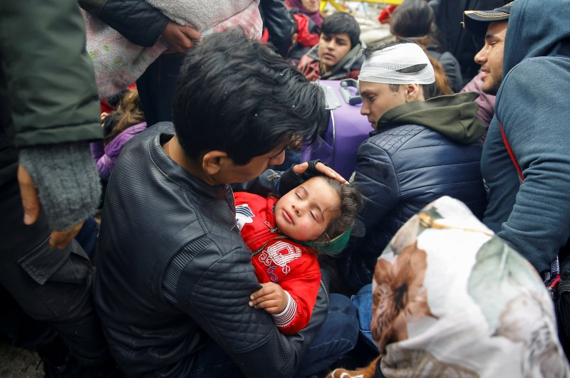 A migrant holds a child at Turkey's Pazarkule border crossing with Greece's Kastanies, in Edirne, Turkey, Feb. 29, 2020. (Reuters Photo)