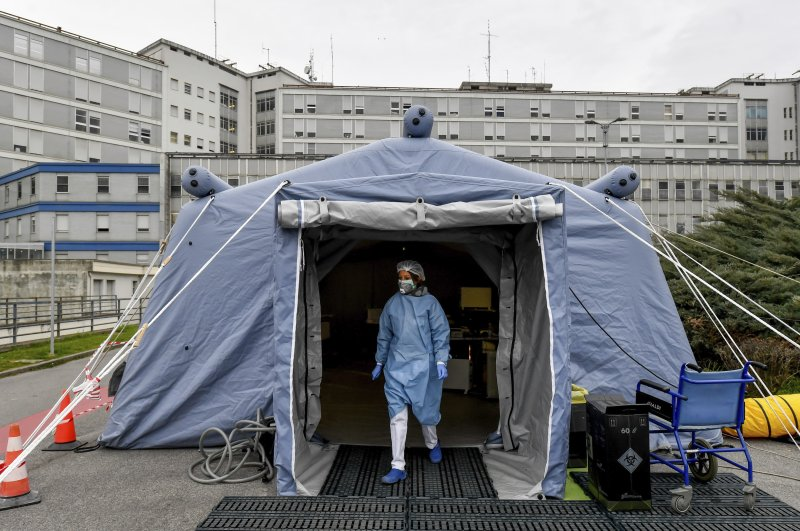 A paramedic walks out of a tent that was set up outside the hospital of Cremona, northern Italy, Saturday, Feb. 29, 2020. (Lapresse via AP)