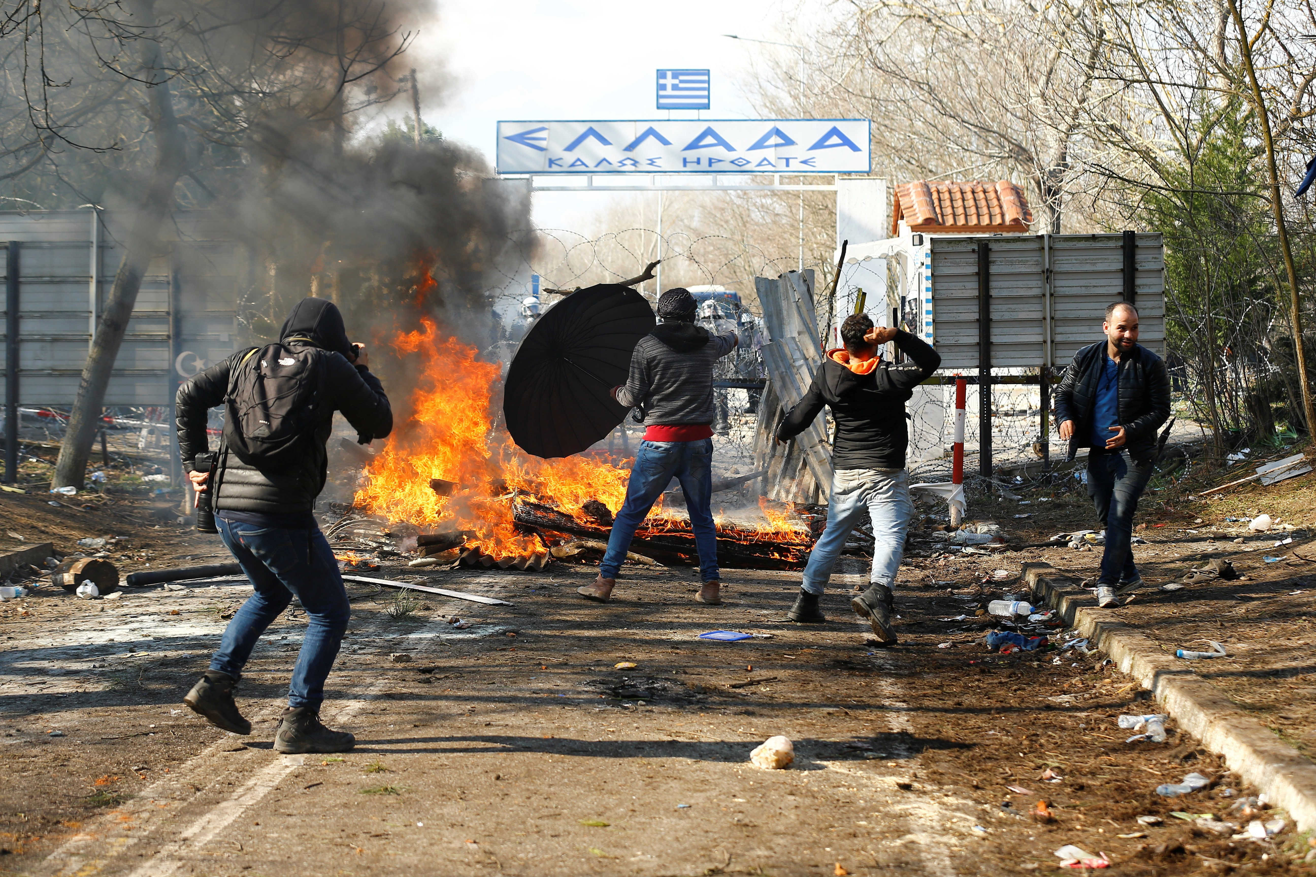 Migrants throw objects during clashes with Greek police, at the Turkey's Pazarkule border crossing with Greece's Kastanies, in Edirne, Feb. 29, 2020. REUTERS