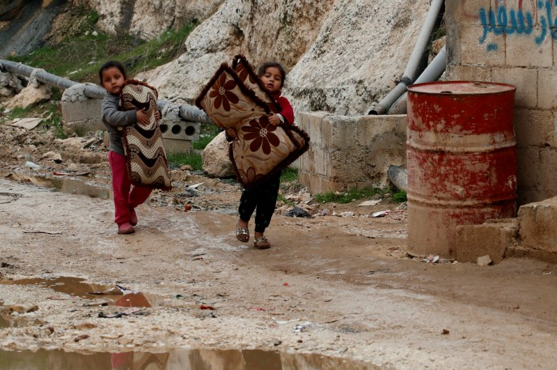 Internally displaced Syrian girls carry their belongings in an IDP camp located in Sarmada in Idlib province, Syria Feb. 28, 2020. (Reuters Photo)