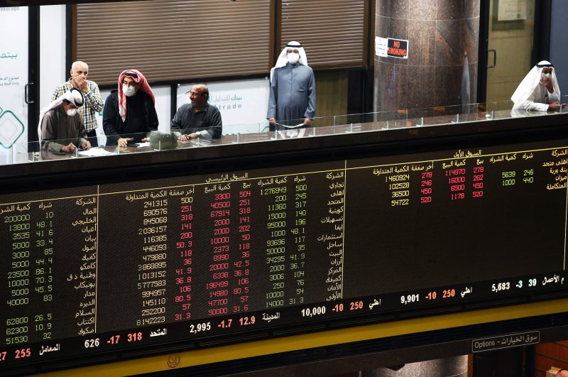 Kuwaiti traders wearing protective masks follow the market at the Boursa Kuwait stock exchange in Kuwait City, March 1, 2020. (AFP Photo)