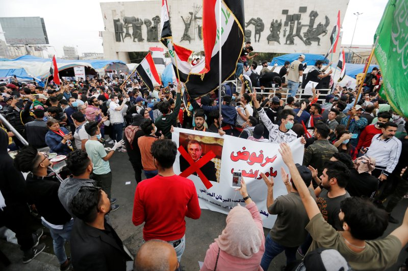 Iraqi demonstrators carry a poster depicting Iraqi Prime Minister Mohammed Tawfiq Allawi, to express their rejection of him, Baghdad, March 1, 2020. (Reuters Photo)