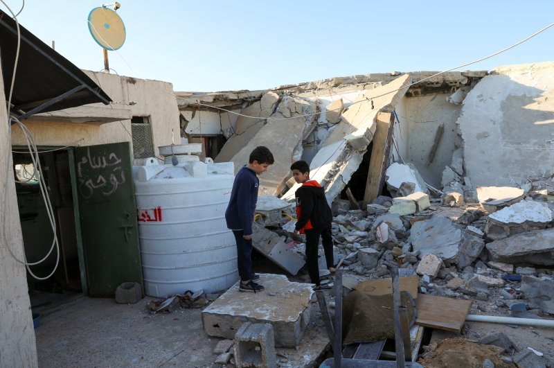Boys stand near a damaged house after shells fell on a residential area, in the Abu Slim district south of Tripoli, Libya, Feb. 28, 2020. (Reuters Photo)