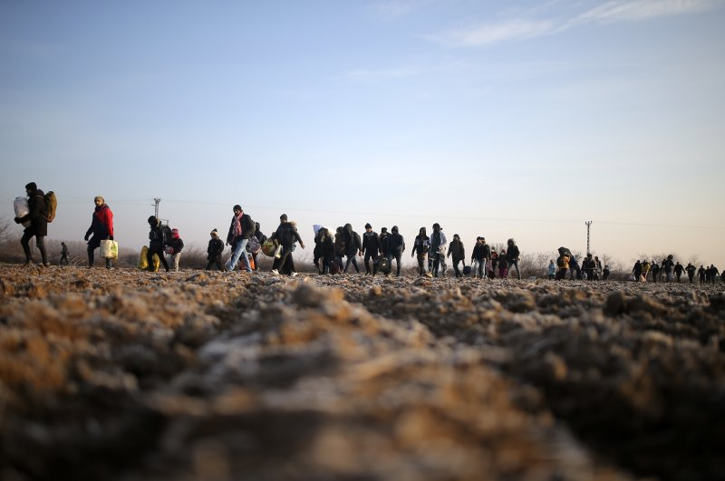 Migrants walk to reach the Pazarakule border gate at the Turkish-Greek border in Edirne, Turkey, March 1, 2020. (AP Photo)