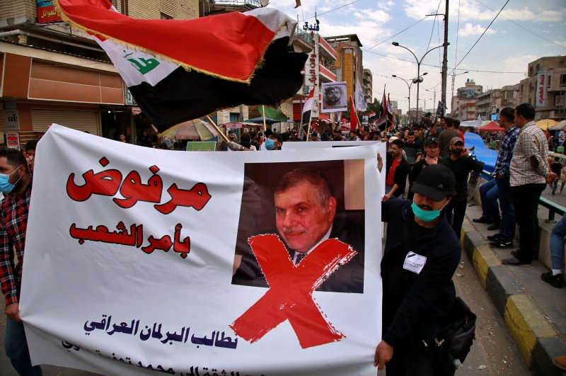"Protesters hold a poster showing Iraq's prime minister-designate, Mohammed Allawi, with Arabic writing that reads, ""Rejected by order of the people,"" during a rally, Baghdad, March 1, 2020. (AP Photo)"