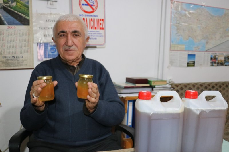 Mehmet Kasım Alageyik poses with jars of what he claims contain the solution to the world's coronavirus problem, Van, March 2, 2020. (İHA Photo)
