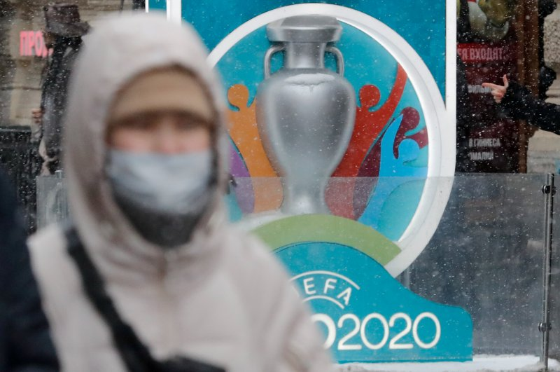 A person wearing a protective face mask walks past the Euro 2020 countdown clock in Saint Petersburg, Russia, March 1, 2020. (Reuters Photo)